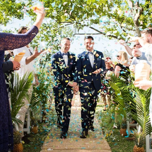 Groom and Groom getting married at Paradise Cove Resort with confetti celebration