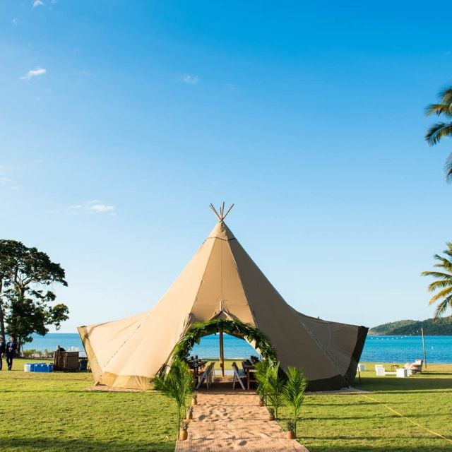 Teepee Wedding Reception set up on lawn with palm trees and ocean backdrop