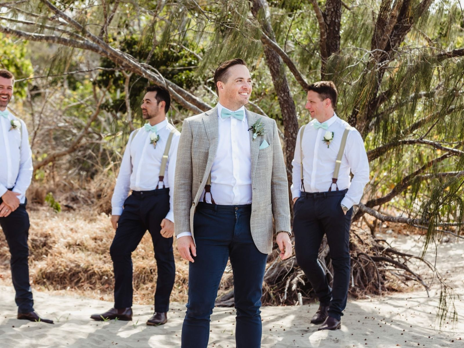 Groom and groomsmen standing on beach by tree at Paradise Cove Resort in the Whitsundays