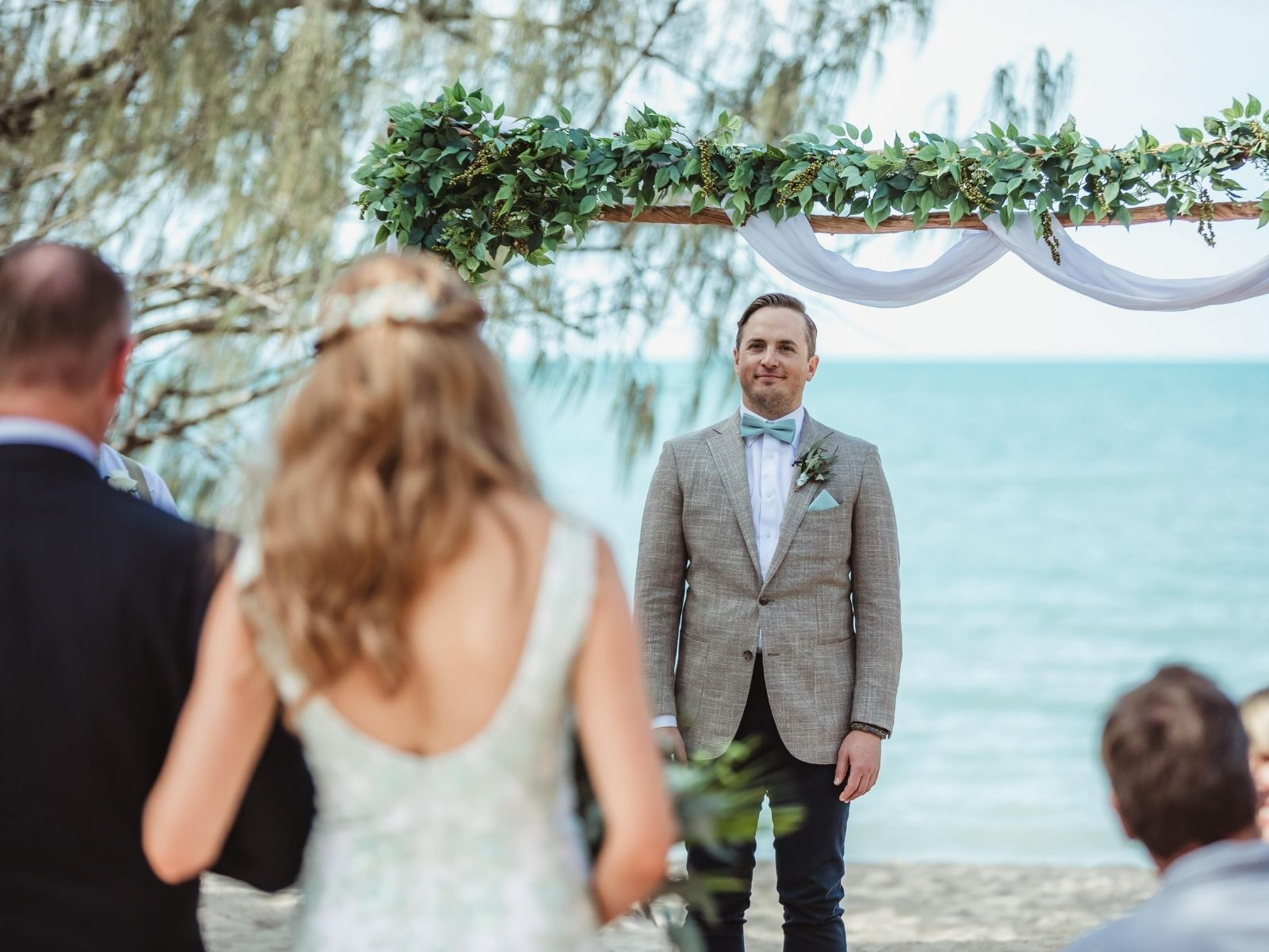 Groom sees bride for the first time as she walks down the aisle at Paradise Cove Resort in the Whitsundays