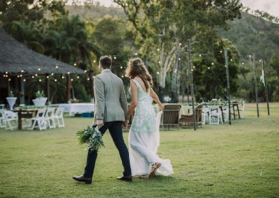 Bride and Groom walking on a lawn at their wedding reception