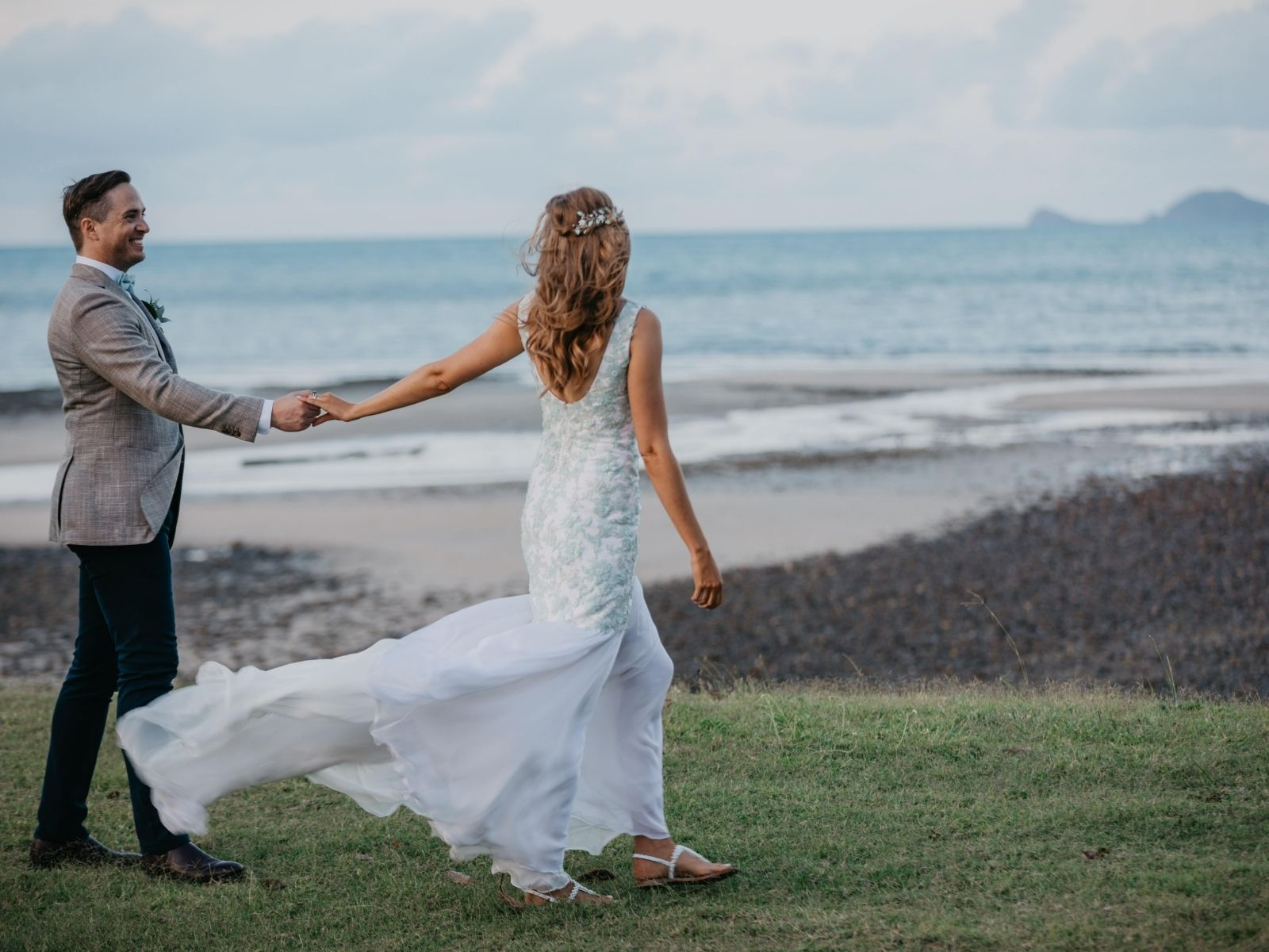 Bride and Groom walking on a beach at sunset at Paradise Cove Resort in the Whitsundays