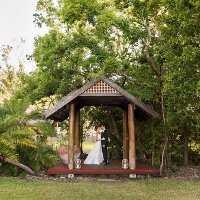 Bride and Groom at wooden pavilion at Paradise Cove Resort