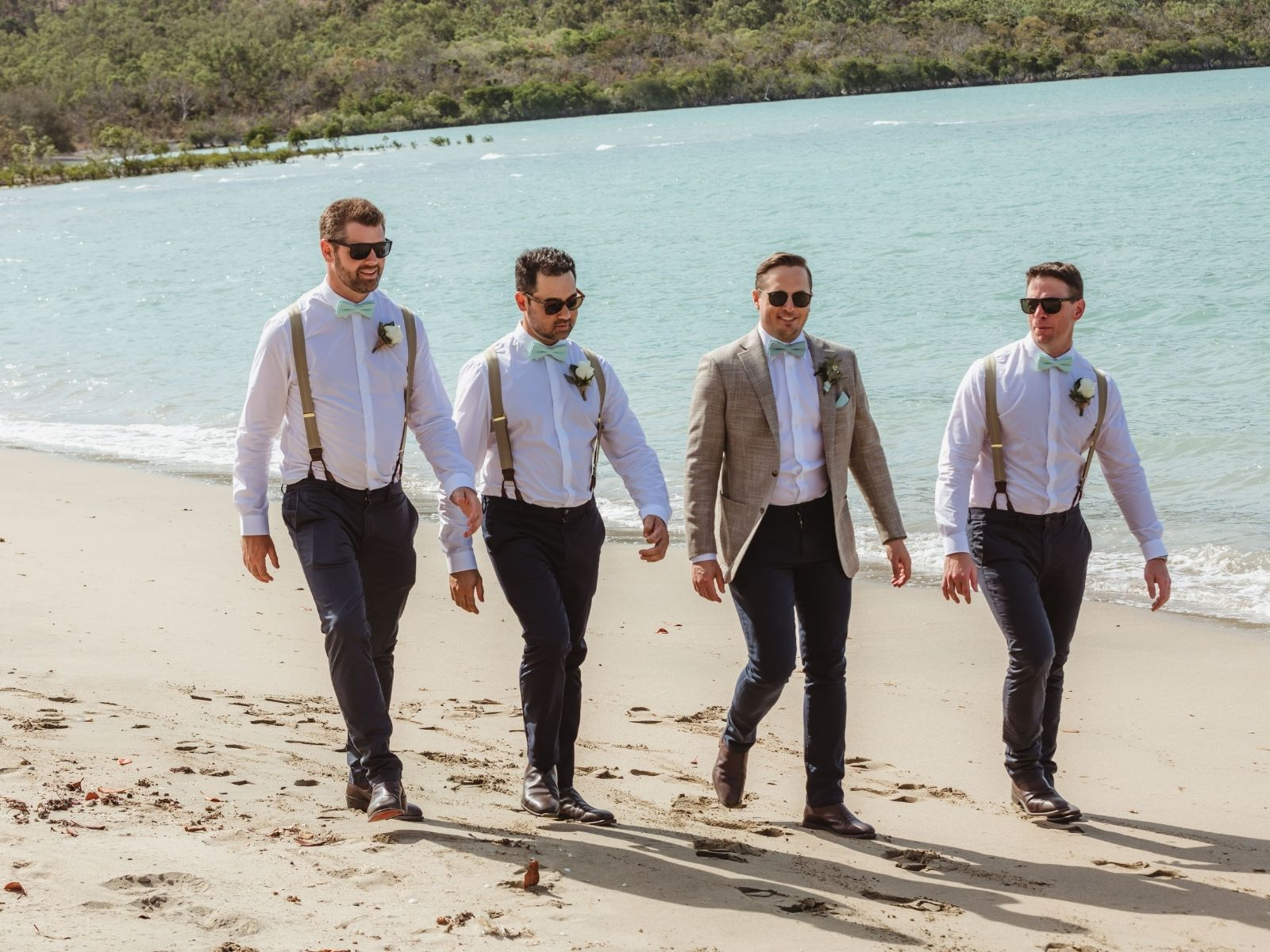 Groom with groomsmen walking on beach at Paradise Cove Resort in the Whitsundays