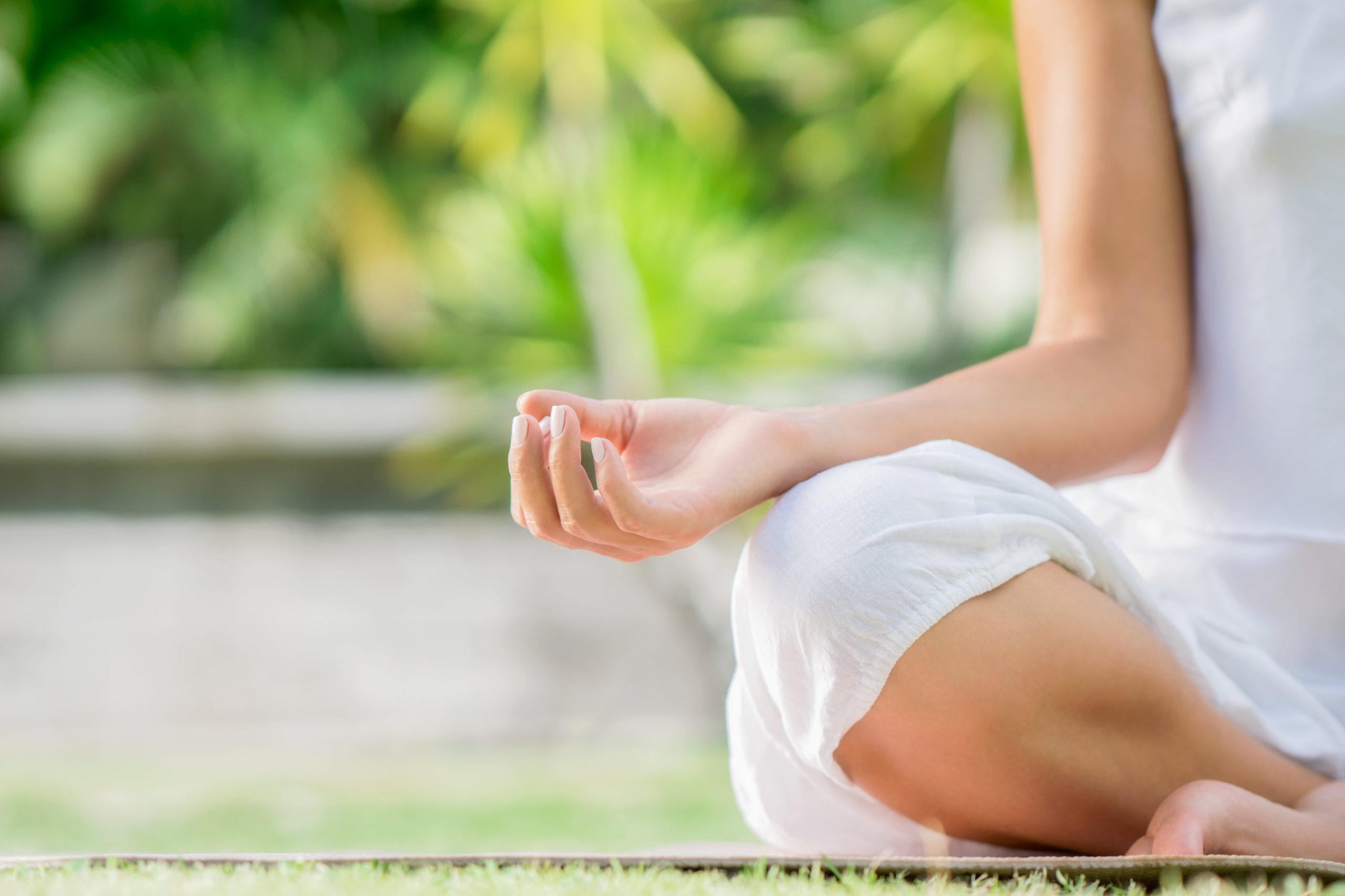 Image of woman meditating during yoga class on the grass