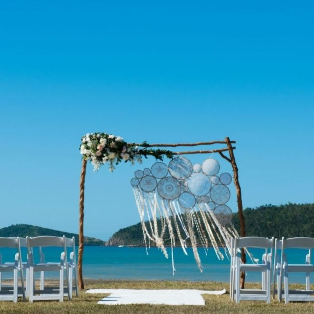Wedding ceremony at Paradise Cove Resort in the Whitsunday, with ocean backdrop on the main lawn