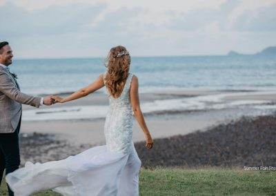 Bride and Groom walking on the oceanfront at Paradise Cove Resort in the Whitsundays