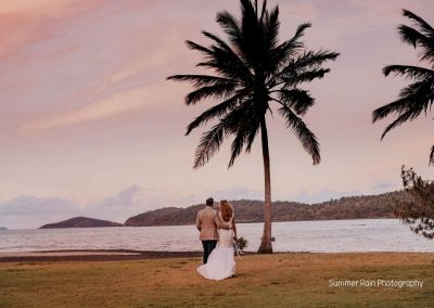 Bride and Groom standing under a palm tree at a pink sunset overlooking the ocean, at Paradise Cove Resort in the Whitsundays
